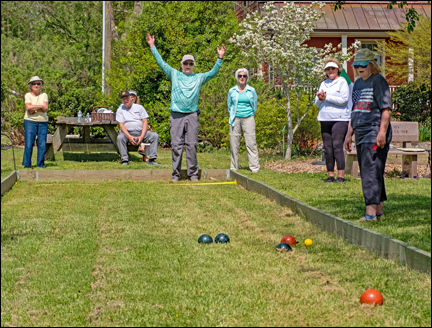 bocce player celebrating a successful ball toss as his teammates look on